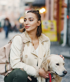 a girl walking a dog in the city
