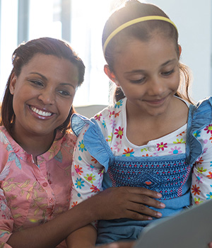 a mother and daughter playing on a laptop